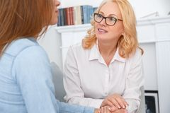 Female psychologyst therapy session with client indoors sitting talking to patient close-up royalty free stock image