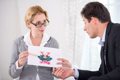 Female psychotherapist holding Rorschach Test Royalty Free Stock Photos