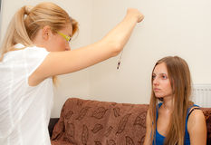 Female psychotherapist hypnotizes a female patient. A sexy female psychotherapist treats a teenage female patient with normal and cliche ways Stock Photography