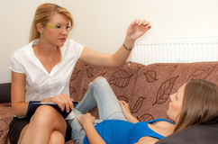 Female psychotherapist hypnotizes a female patient. A sexy female psychotherapist treats a teenage female patient with normal and cliche ways Royalty Free Stock Image