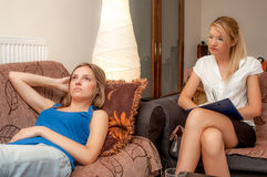 A female psychotherapist treats a female patient. A sexy female psychotherapist treats a teenage female patient with normal and cliche ways Royalty Free Stock Photography