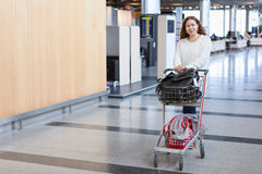 Female pulling luggage hand-cart in airport hall Royalty Free Stock Photos