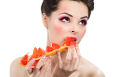 Female with pummelo slice. Female face with pummelo slice over white background Royalty Free Stock Image
