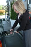 Female pumping gas. Stock Photo