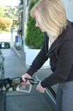 Female pumping gas. Royalty Free Stock Images