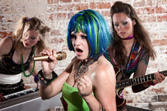 Female Punk Rock Band. Young all girl punk rock band performs in a warehouse Stock Photo