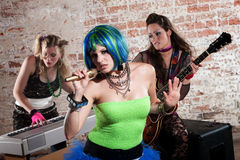 Female punk rock band. Young all girl punk rock band performs in a warehouse Royalty Free Stock Photos