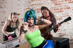 Female punk rock band. Young all girl punk rock band performs in front of brick wall Stock Image