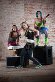 Female punk rock band. Young all girl punk rock band performs in front of brick wall Stock Photo