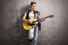 Female punker playing an electric guitar. And leaning against a rusty gray wall stock images