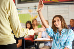 Female Pupil Answering Question In Classroom Stock Images
