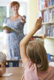 Female Pupil Answering Question In School Classroom Stock Image