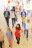 Female Pupil In Classroom Surrounded By Moving Students Royalty Free Stock Photography