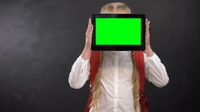 Female pupil closing face with green screen tablet, modern educational system stock video footage