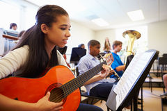 Female Pupil Playing Guitar In High School Orchestra. Close Up Of Happy Female Pupil Playing Guitar In High School Orchestra Stock Photos