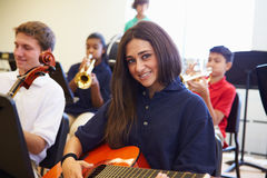 Female Pupil Playing Guitar In High School Orchestra. Smiling At Camera Stock Photos