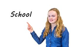 Female pupil points to word School on whiteboard royalty free stock photography