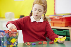 Female Pupil Practising Maths At Desk Stock Photo