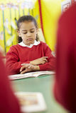 Female Pupil Reading Book At Table Stock Photo