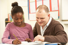 Female Pupil Studying in classroom with teacher Stock Image