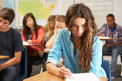 Female Pupil Studying At Desk In Classroom Stock Photos
