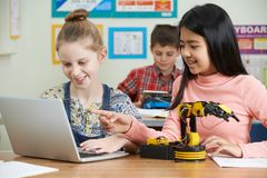 Female Pupils In Science Lesson Studying Robotics. Two Female Pupils In Science Lesson Studying Robotics Royalty Free Stock Images