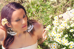 Female purity. Beautiful woman with daisies on the lawn. Closed eyes. A girl relaxed serene on the green grass, flowers beside her. Purity and serenity concept Stock Photos