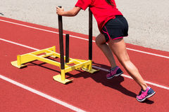 Female pushes a yellow sled on a track at practice Stock Photo