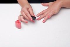 Female putiing nail polish Stock Images