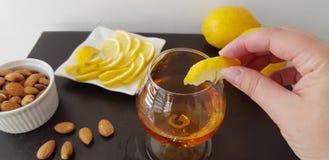 Female puts a slice of lemon on glass half full with brandy stock photos