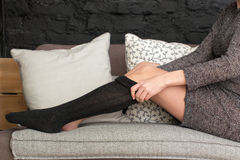 Female putting on black stockings Royalty Free Stock Image