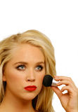 Female putting on face makeup. Cute blonde girl putting on face makeup foundation or rouge, vertical face closeup with copy space Royalty Free Stock Photos