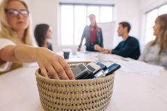 Digital detox - Network at meetings without your cell phones. Female putting her cell phone in a basket while attending a board room meeting in her office. No stock images