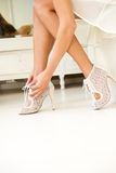 Female putting on high heal shoes. Low angle female putting on high heal shoes indoors stock image