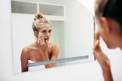 Female putting on moisturizer on her facial skin. Reflection of a female in mirror rubbing cosmetic cream on her face. Female putting on moisturizer on her Royalty Free Stock Photos