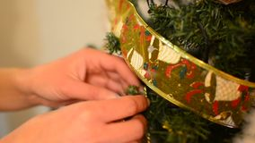 Female is putting ribbon ornament on Christmas tree, closeup Stock Photo