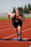 Female race. A female athlete launching off the start line in race Royalty Free Stock Photo
