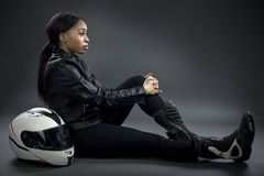 Female Race Car Driver or Stunt Woman or Motorcyclist. Black female wearing leather and helmet posing in a studio as a race car driver, motorcycle rider, or a royalty free stock image