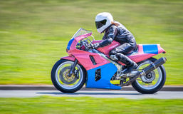 Female racer on motorbike Royalty Free Stock Image
