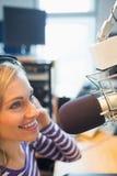 Female radio host broadcasting in studio Stock Photography