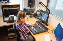 Female radio host operating sound mixer. At desk in studio Stock Photos