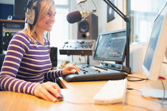 Female radio host using computer while broadcasting Stock Image