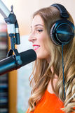 Female radio presenter in radio station on air. Female presenter or host in radio station hosting show for radio live in Studio royalty free stock photography