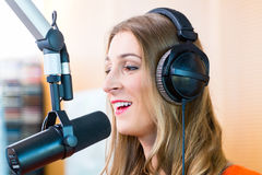 Female radio presenter in radio station on air. Female presenter or host in radio station hosting show for radio live in Studio royalty free stock photo