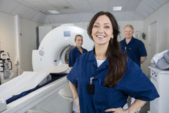 Female Radiologist With Colleagues Standing By MRI Machine. Portrait of happy female radiologist with colleagues standing by MRI machine in hospital stock photos