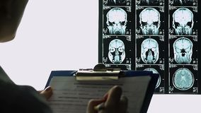 Female radiologist filling out medical report, describing brains mri, conclusion stock video
