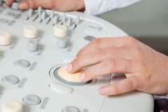 Female Radiologist Operating Ultrasound Machine. Close up of female radiologist operating ultrasound machine Stock Photo