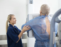 Female Radiologist Taking Chest Xray Of Mature Patient Stock Photo