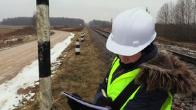 Female railway worker checking warning signs. In cold winter day stock video footage