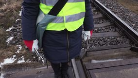 Female railway worker with wrenches in hands. On railway in winter stock video